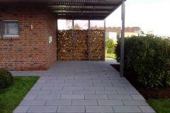 Carport mit Holzwand und Zufahrt